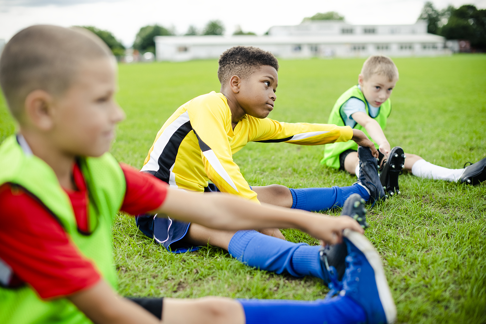 3 unger i ulik fotballtrøyer som tøyer på gresset